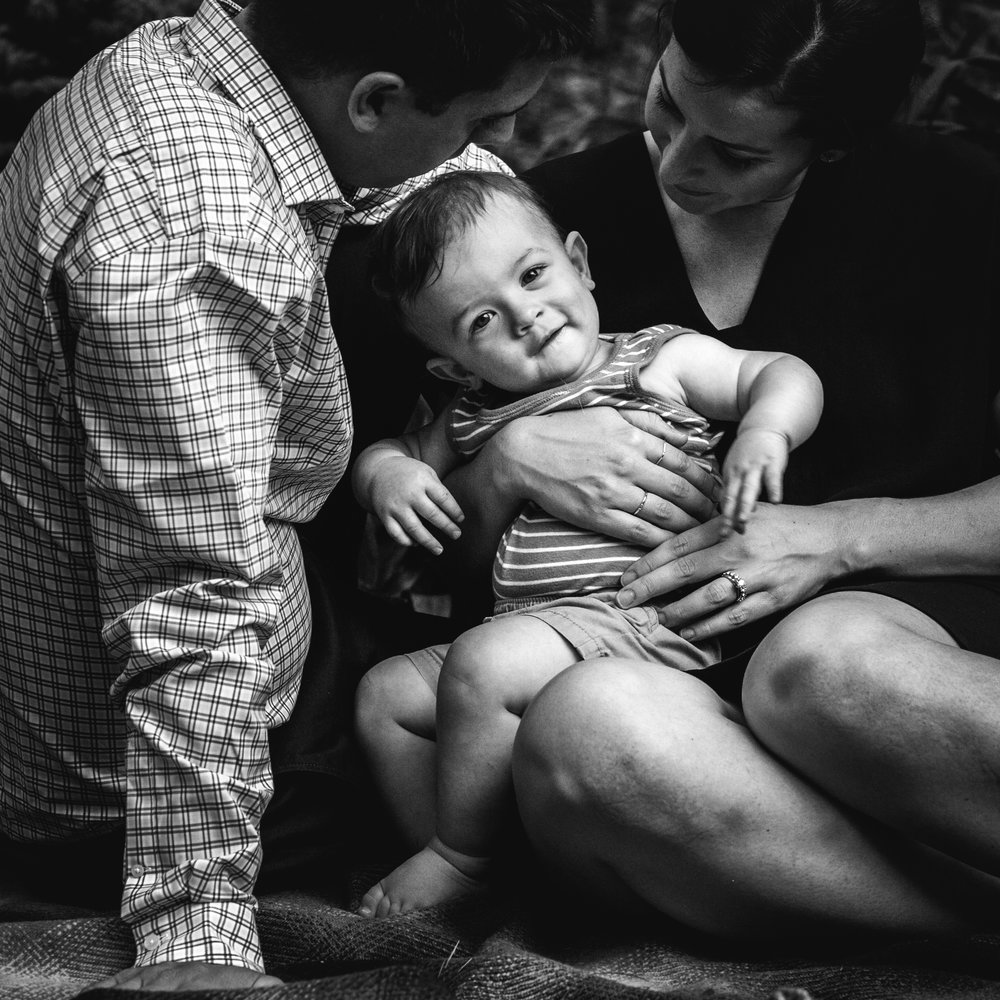 black and white photograph of smiling boy looking at camera while sitting in moms lap with dad near by