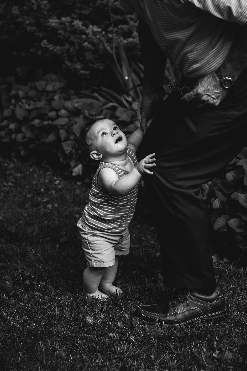 black and white photograph of toddler holding on to parent's let and looking up
