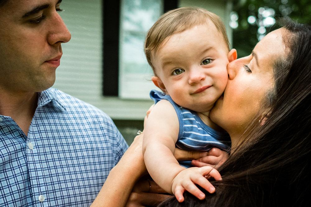 mom kisses baby son's cheek