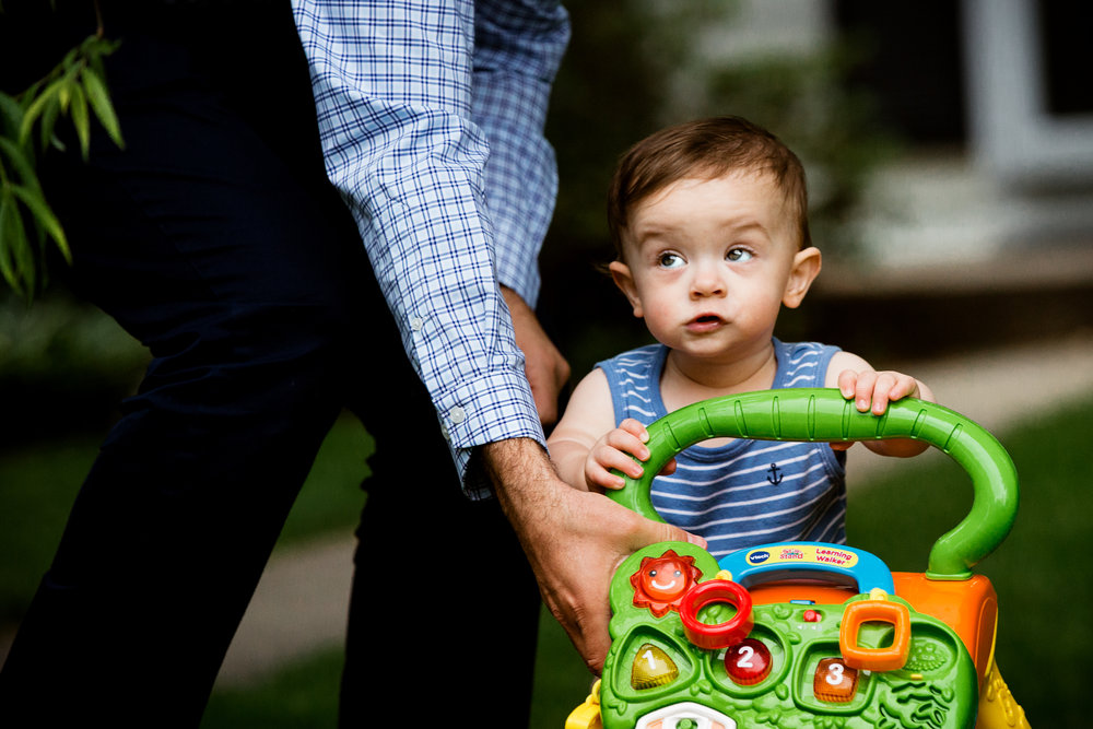 young toddler boy walks using walking toy outside grandparents' home