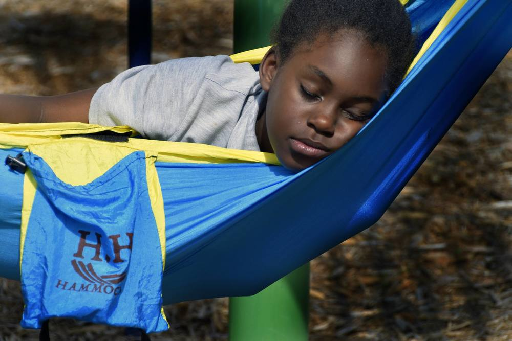 A young girl at The Family Promise Homeless shelter in Chattanooga TN, takes a nap in a hammock.