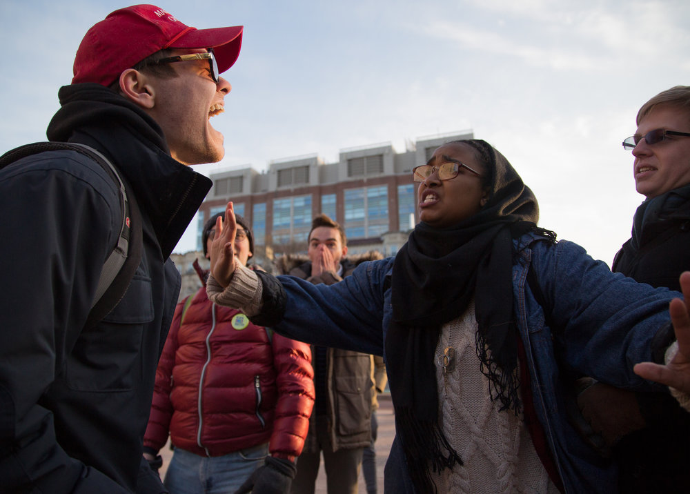 "Boston University Freshman and Trump Supporter Nicholas Fuentes (left) laughs as he is confronted by a protester during the ""No Ban No Wall: Rally Against Xenophobia"" on Jan. 30, 2017 in Boston. The protest was one of many throughout the country in response to President Trump's executive order to prohibit travelers from certain countries."