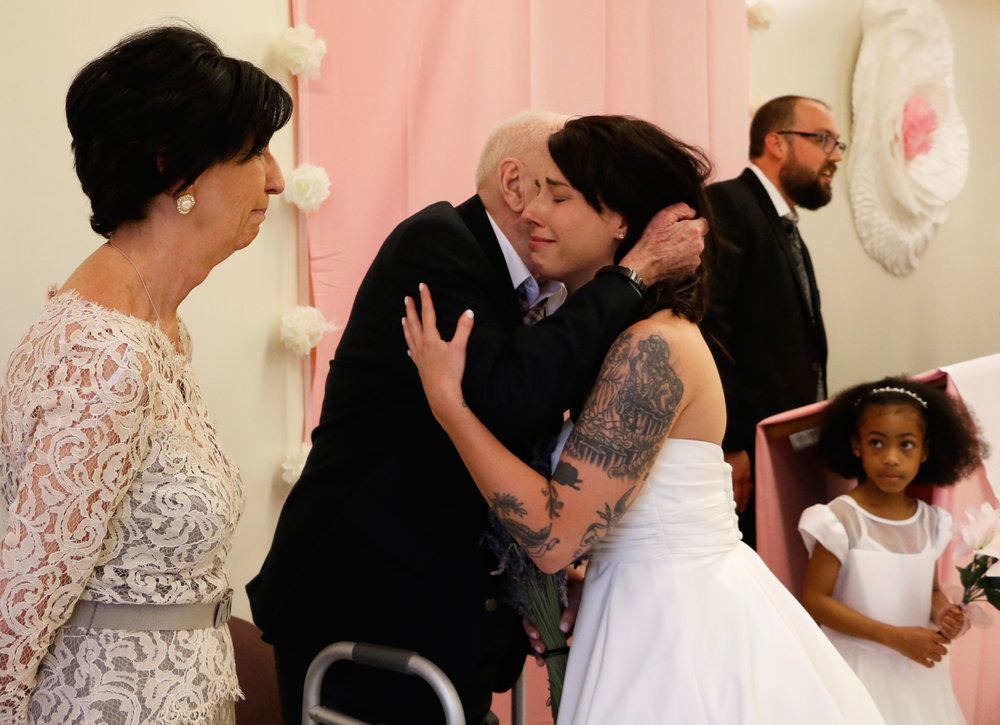 Diane (far left) and Frederic Hoit (second from left) greet their daughter Kate (center) inside the Albany County Nursing Home on June 6, 2015 in Albany, N.Y. Kate and her husband Alexander Borisov, both army veterans living in Virginia, decided to have a ceremony in the nursing home so Kate's father, who has Alzheimers Disease, could be a part of the ceremony.