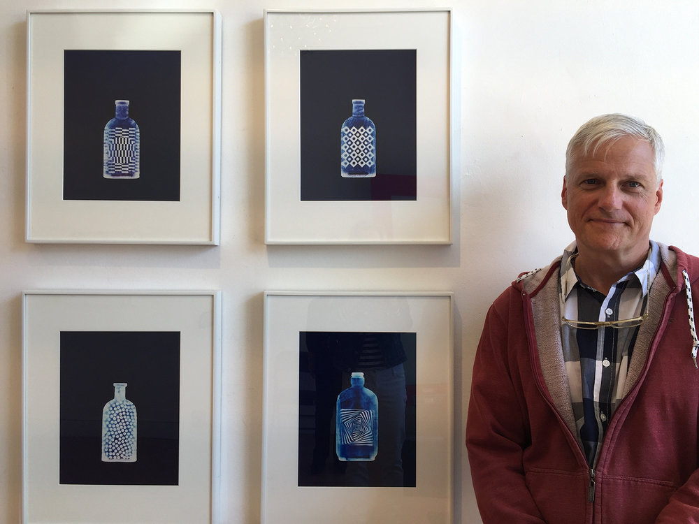 Greg Wilson standing beside a collection of his C Prints.