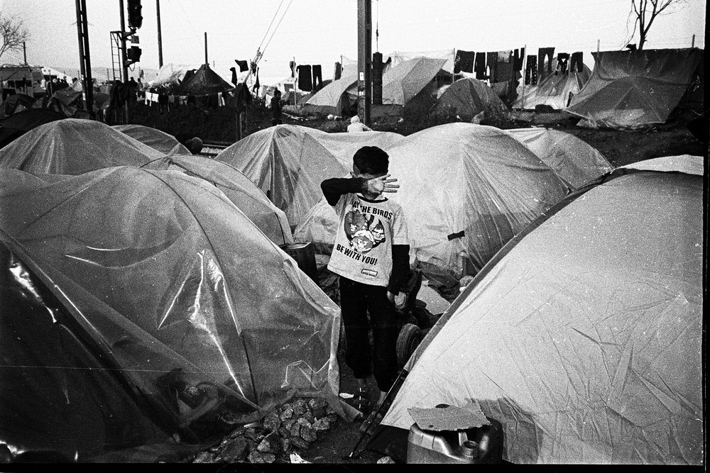 Angry birds.  Syrian boy standing in between his family's tents at the Idomeni refugee camp.