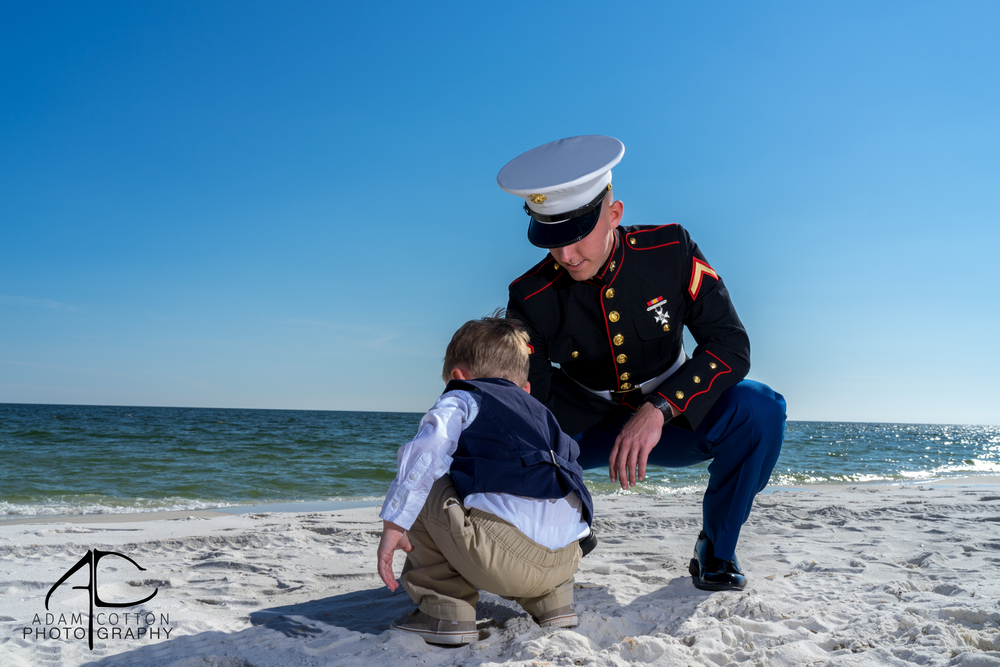 image of groom playing in sand with nephew before wedding by pensacola photographer adam cotton