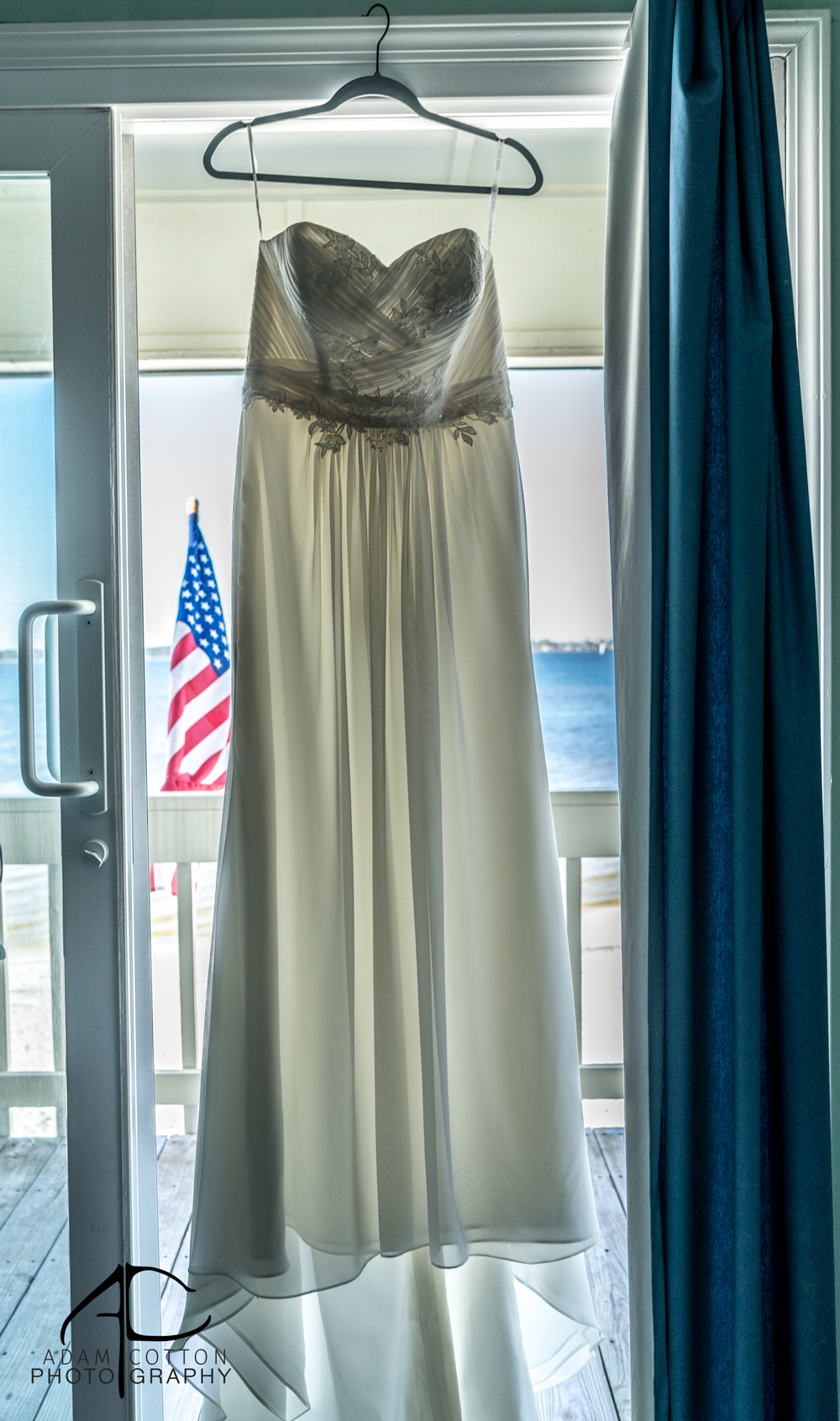 image of wedding dress in doorway backlit with american flag in background by photographer adam cotton