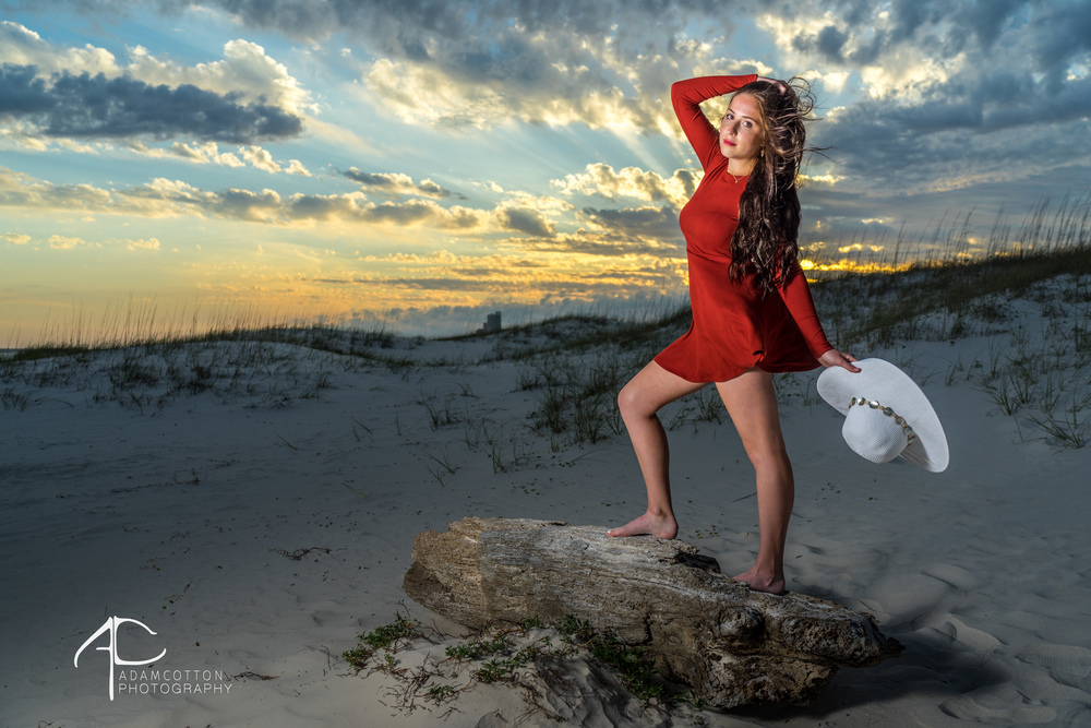 portrait photoshoot with model holding sun hat at sunset at orange beach alabama