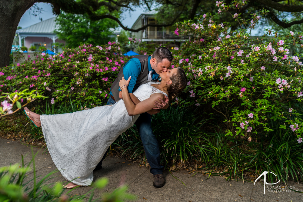 groom_dipping_bride_and_kissing_flowers_behind.jpg
