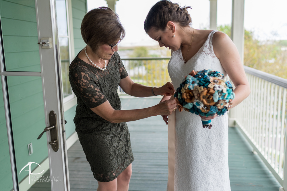 candid image lee house mother tying brides dress with bouquet by pensacola wedding photographer adam cotton