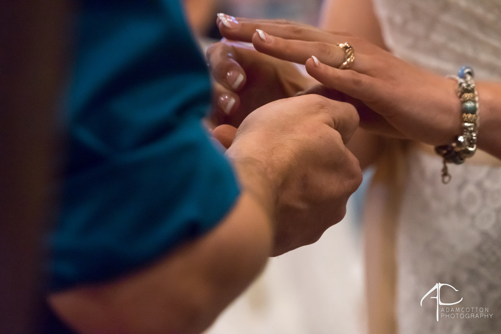 close up image of bride and groom exchanging rings wedding ceremony pensacola wedding venue lee house