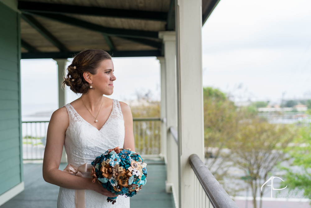 image brude gazing out with wedding dress and veil on pensacola lee house terrace photographer adam cotton