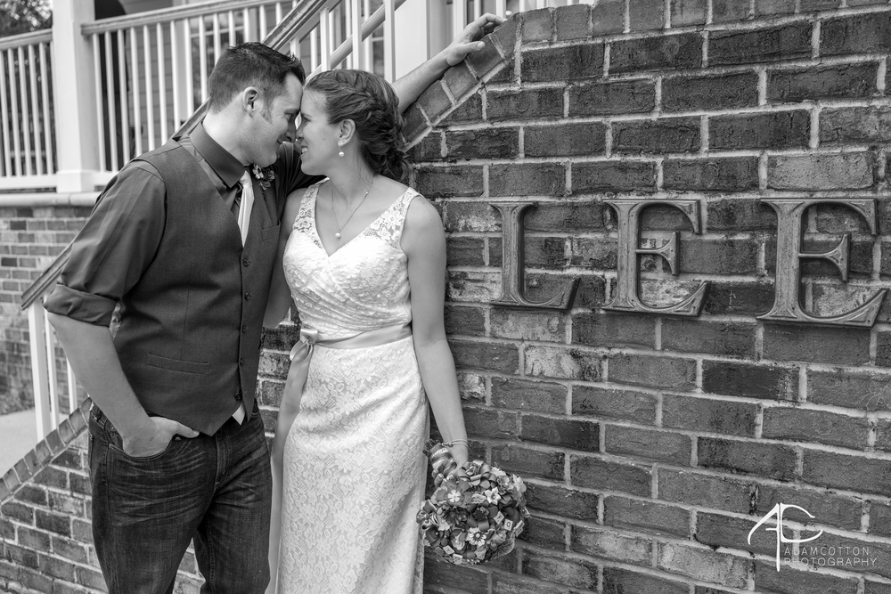 black and white image groom bride smiling in front of pensacola wedding venue Lee house venue sign