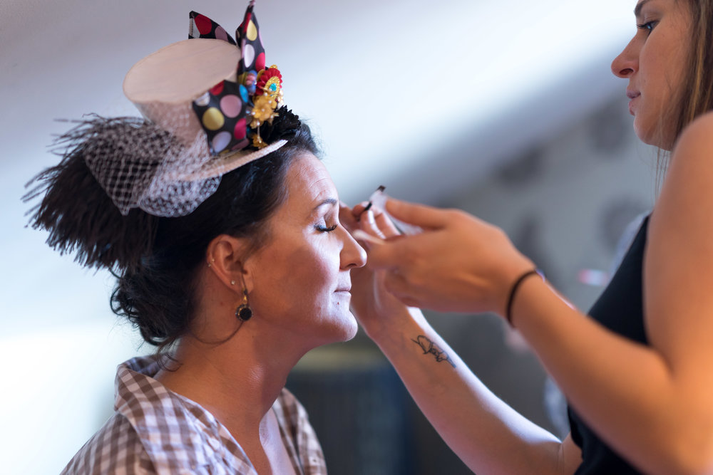 close up image of makeup artist and bride with hat getting ready by pensacola wedding photographer