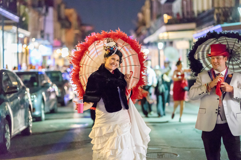 wedding parade with bride and groom and parasol down the french quarter by wedding photographer