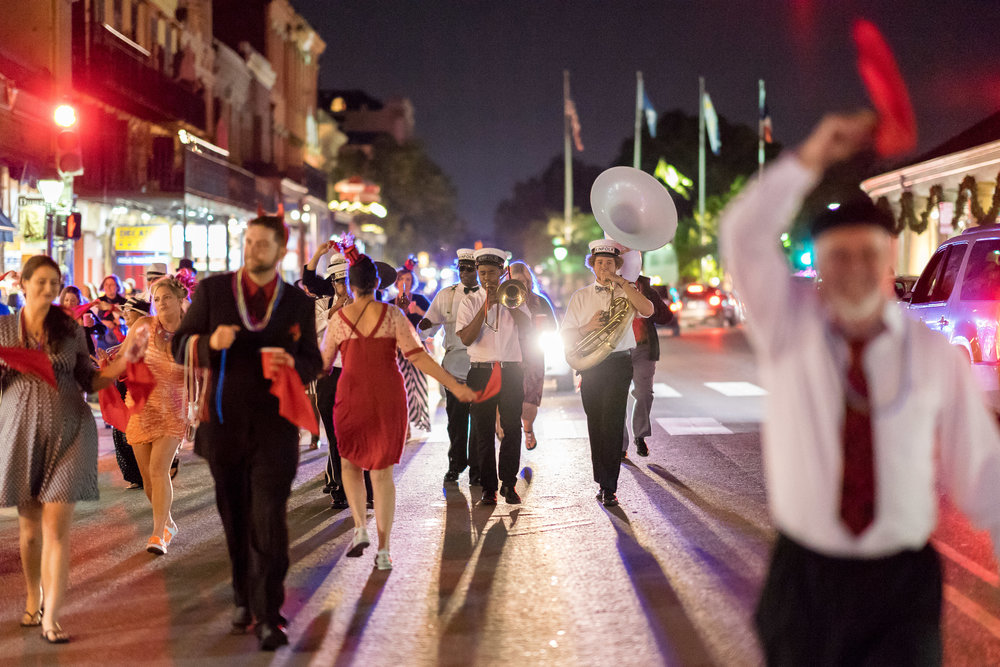 image of bridal party and marching band parade down french quarter