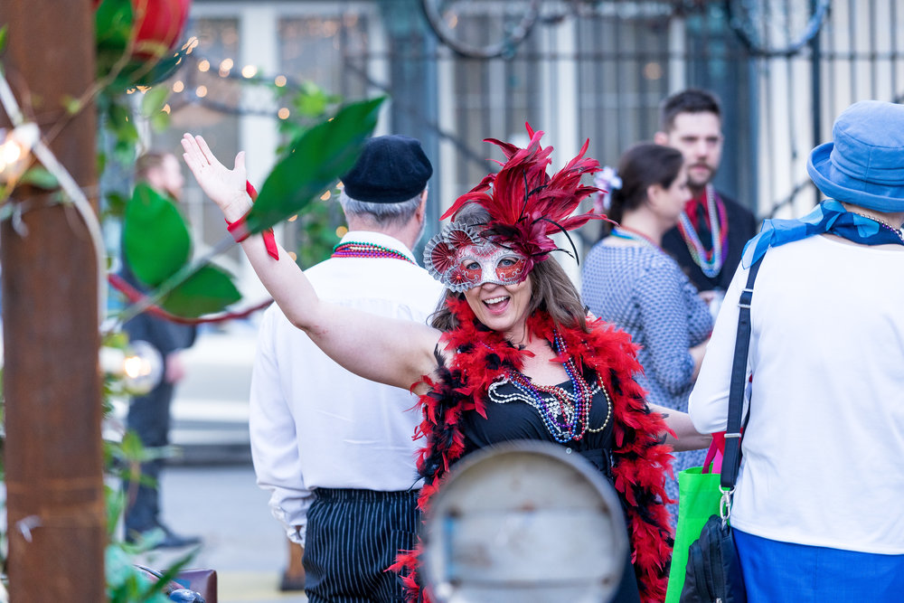 image of mardi gras attire girl waving during wedding ceremony in french quarter destination wedding photographer