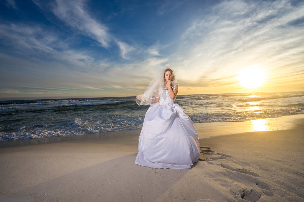 image of beautiful bride on pensacola beach with wedding dress and veil by photographer adam cotton
