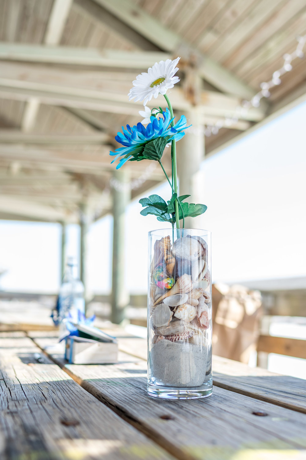 image of glass of sand and flowers detail shot from a pensacola beach wedding