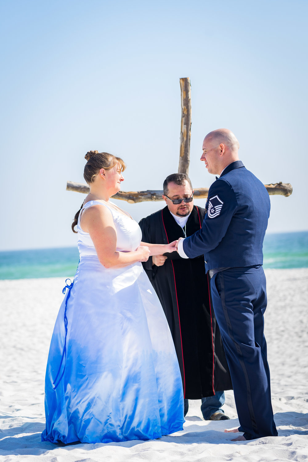 image of couple holding hands during pensacola beach wedding ceremony by photographer adam cotton