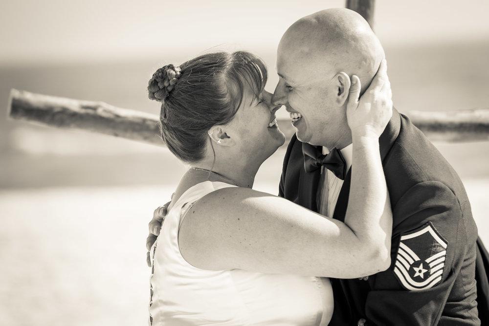 black and white image of kiss by bride and groom at pensacola beach wedding ceremony by photographer adam cotton