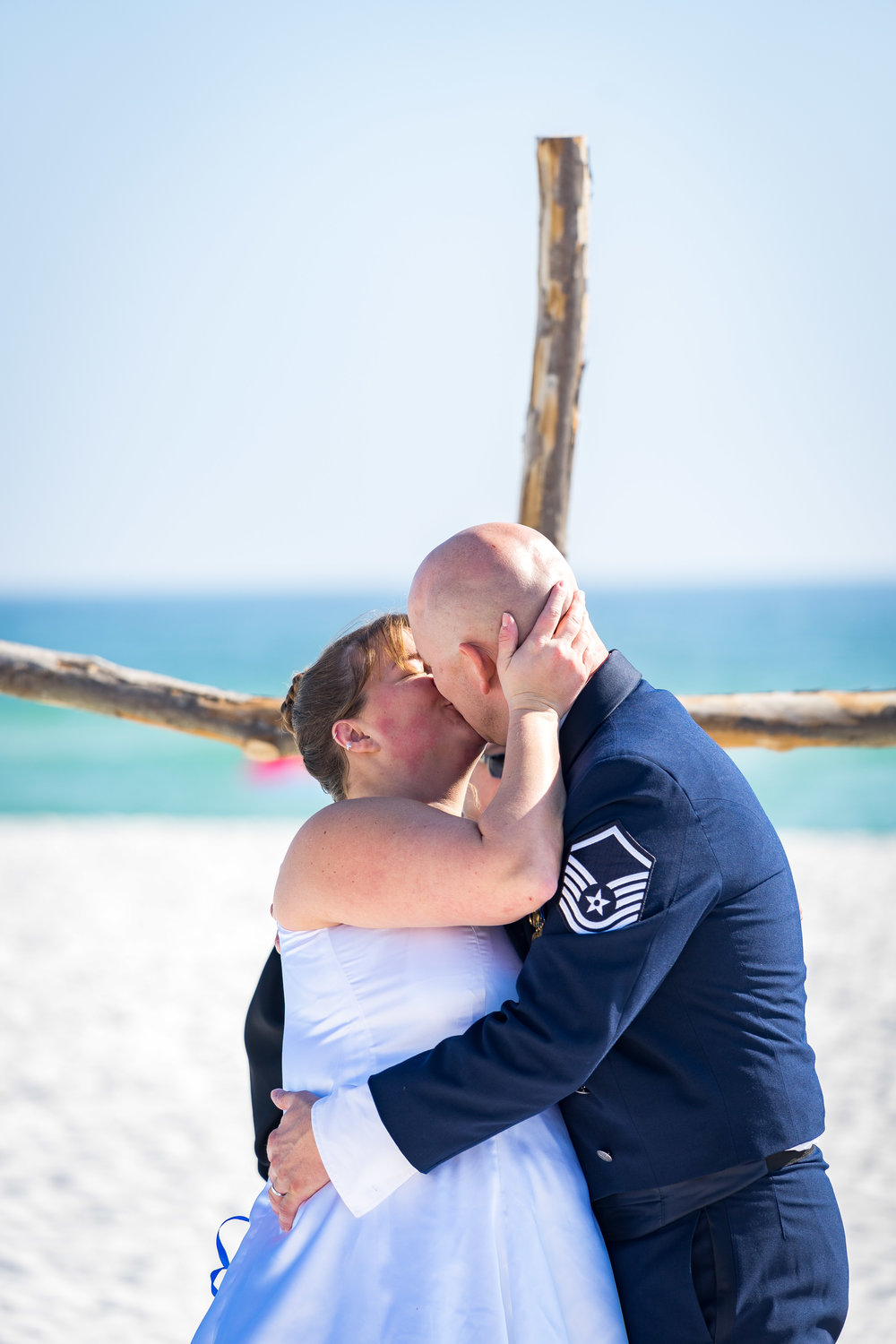 image of bride and groom kissing during pensacola beach wedding ceremony  by photographer adam cotton
