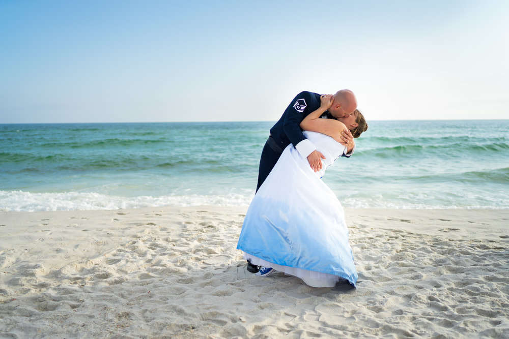 image of wedding couple dipping and kissing by the shore pensacola wedding