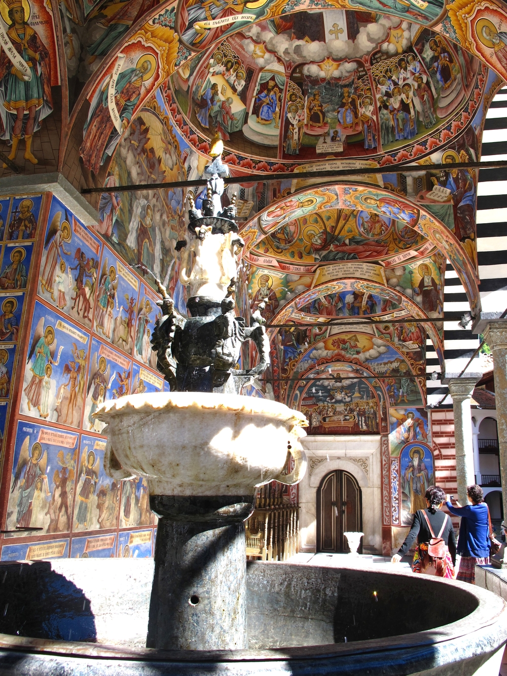 We are greeted by this golden dove fountain shimmering in sunlight.  Water splashes into the basin and birds sing from nearby trees.    © Evelyn Weliver  Church of the Nativity, Rila Monastery, Bulgaria