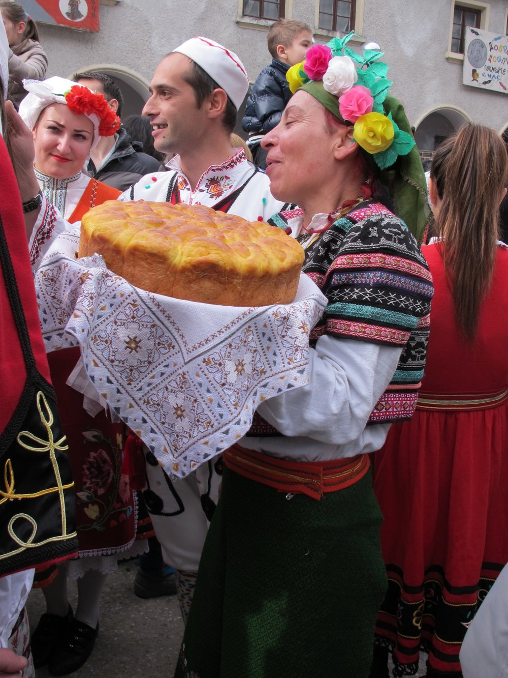 Guests are welcomed into the home with bread and salt.  Mummers' Festival, Shiroka Laka, Bulgaria.  ©   Evelyn Weliver