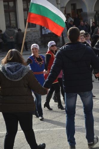 DSC_7750 The horo dance is led by a woman holding the Bulgarian flag.  Kukeri Festival, Shiroka Laka, Bulgaria. © Del Weliver