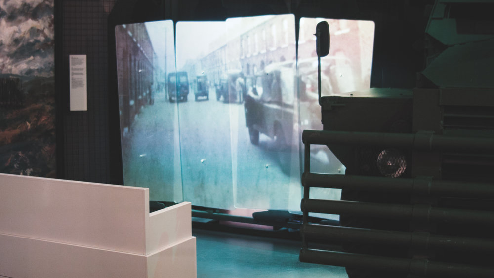 "The completed look of the projection mapped ""Conflict in our streets"" video onto perspex riot shields in the Northern Ireland exhibition space."