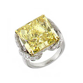 FANCY YELLOW RADIANT CUT DIAMOND WITH COLORLESS ROUND DIAMONDS IN A SCHLUMBERGER STYLE RING CRAFTED IN 18K YELLOW GOLD AND PLATINUM, 22.07 CTW, TOP VIEW