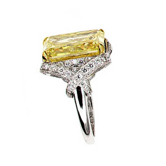 FANCY YELLOW RADIANT CUT DIAMOND WITH COLORLESS ROUND DIAMONDS IN A SCHLUMBERGER STYLE RING CRAFTED IN 18K YELLOW GOLD AND PLATINUM, 22.07 CTW, SIDE VIEW