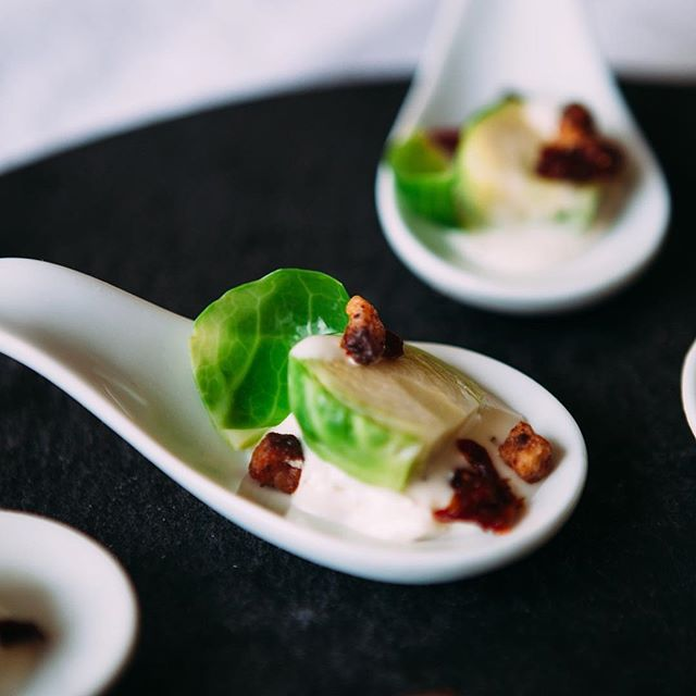 "Our version of a ""wedge"" salad starter... Brussels sprouts + pancetta + Roquefort cream. #passedhorsdoeuvres #classicsrevisited #onebiters #cateringclt #cltcatering #frcustomcatering"