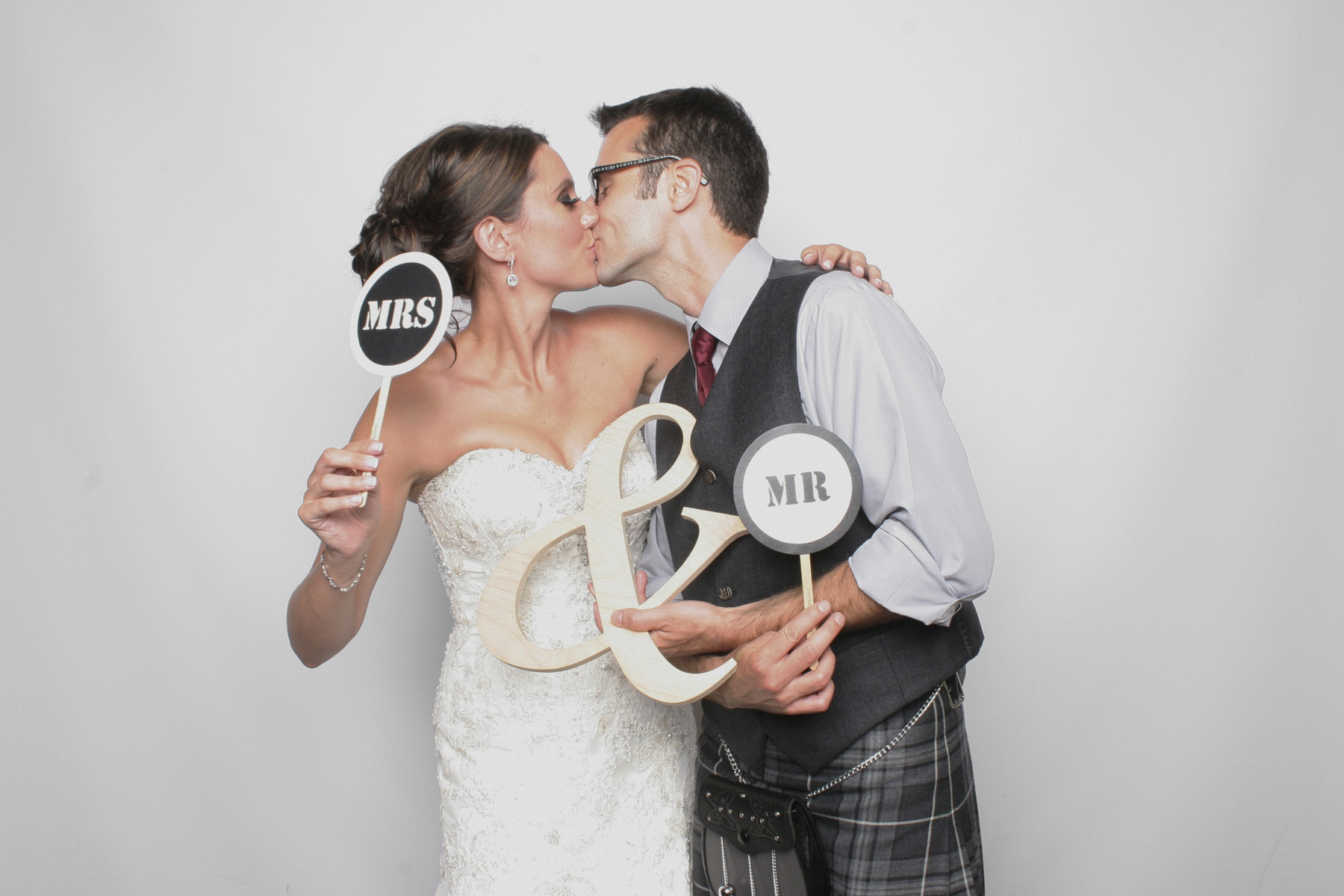 The bride and groom from a Scottish wedding kissing in the photo booth.