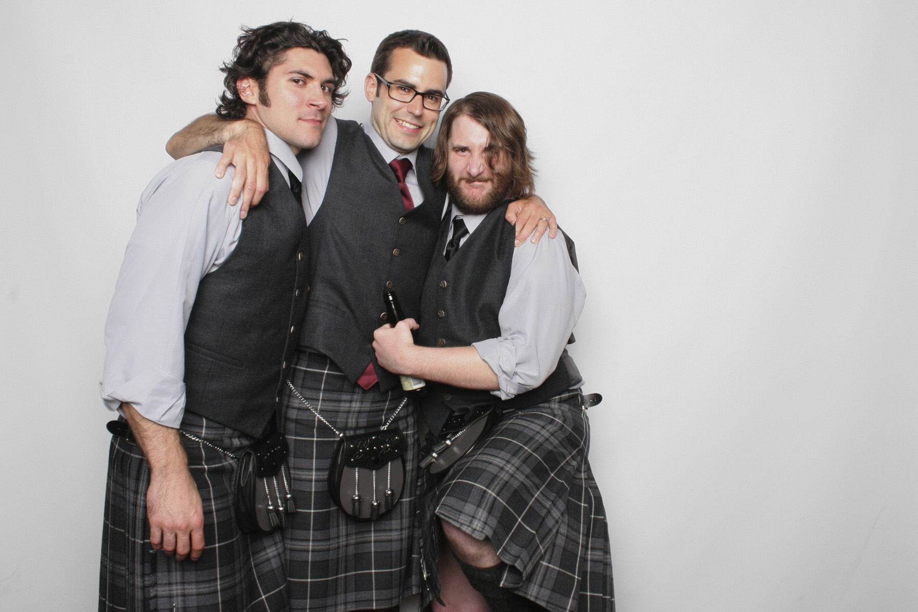 Men from the grooms party wearing Scottish kilts pose together in the photo booth.