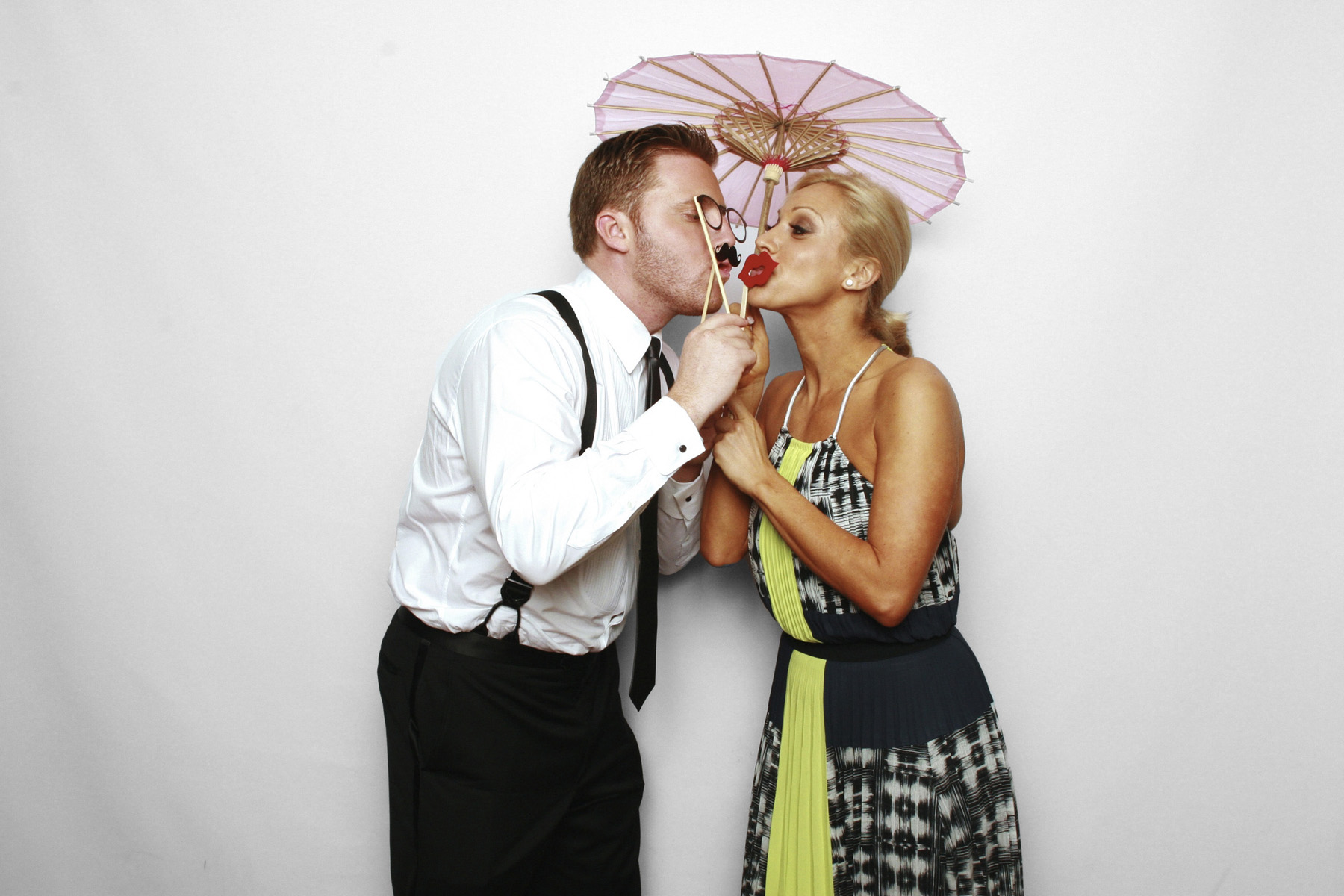 New York City Photo Booth at Chelsea Piers with couple holding umbrella and stick props