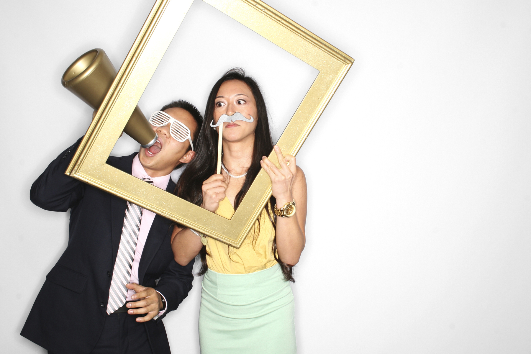 Couple with props and frame in New York Photobooth