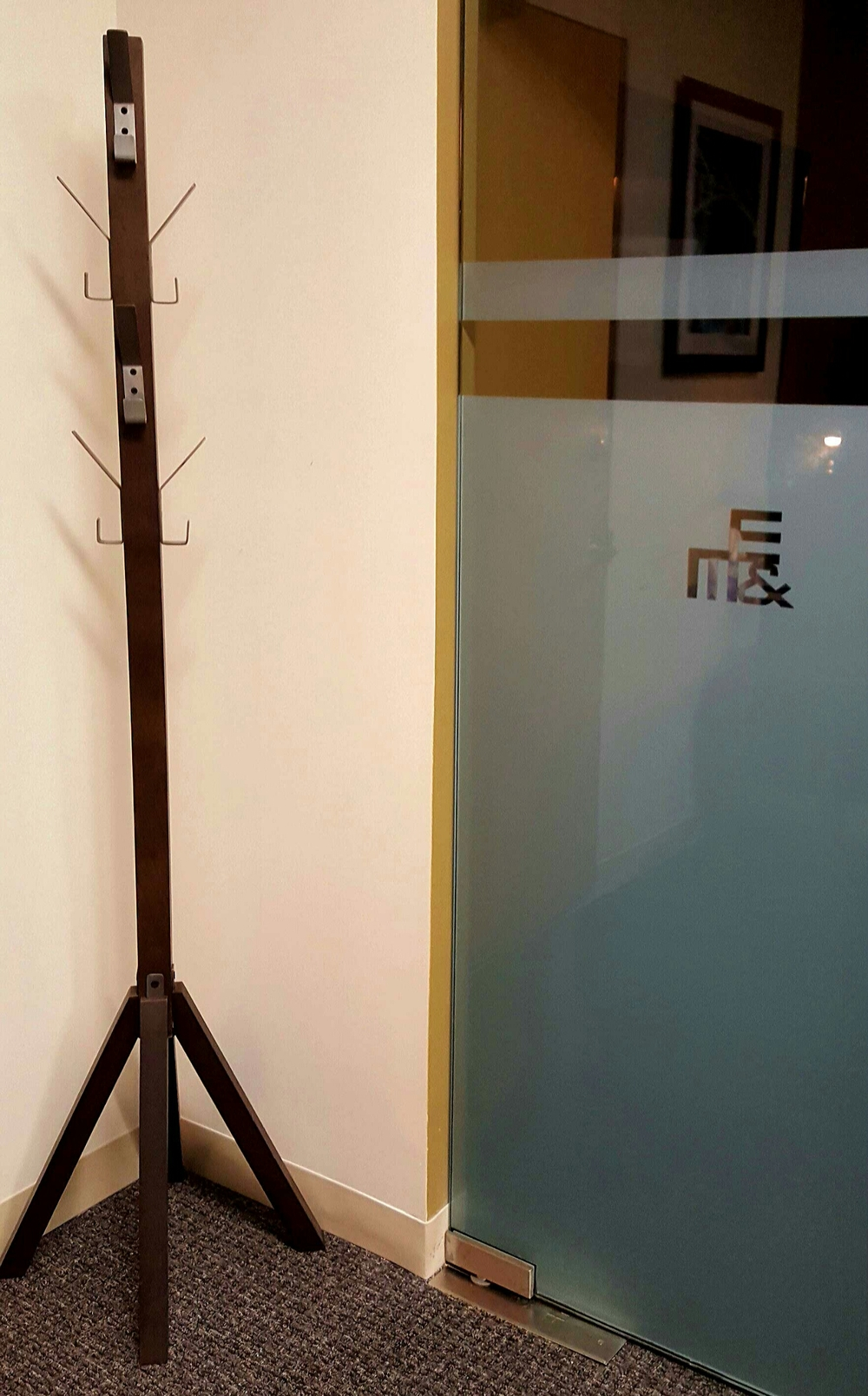 Industrial looking Leigh coat rack from Crate and Barrel fit perfectly in the corner for the outerwear of clients.