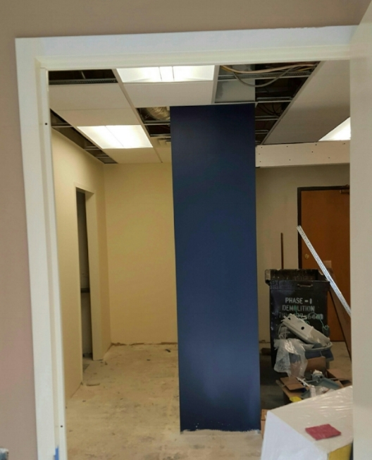 The Gentlemen's Gray colored wall by Benjamin Moore creates a cove for the paralegal's work area, at the same time introducing a bold color pop for clients entering into the reception area.