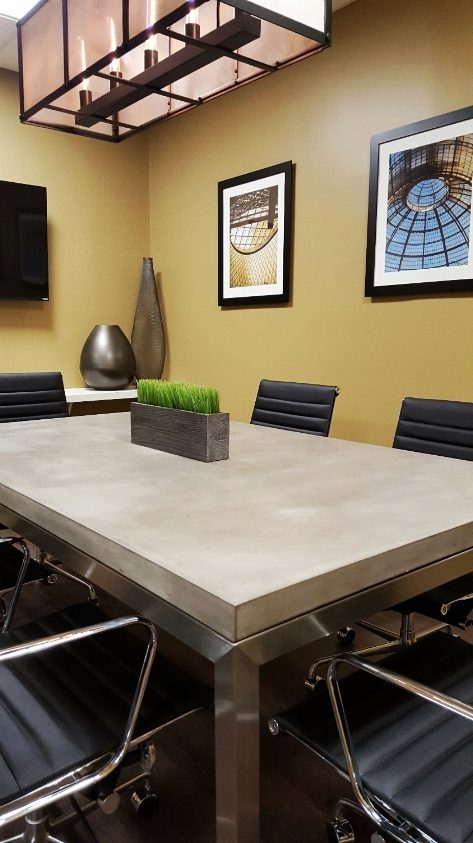 The concrete table top and brushed steel base from Crate and Barrel define the conference room with strength and eloquence.