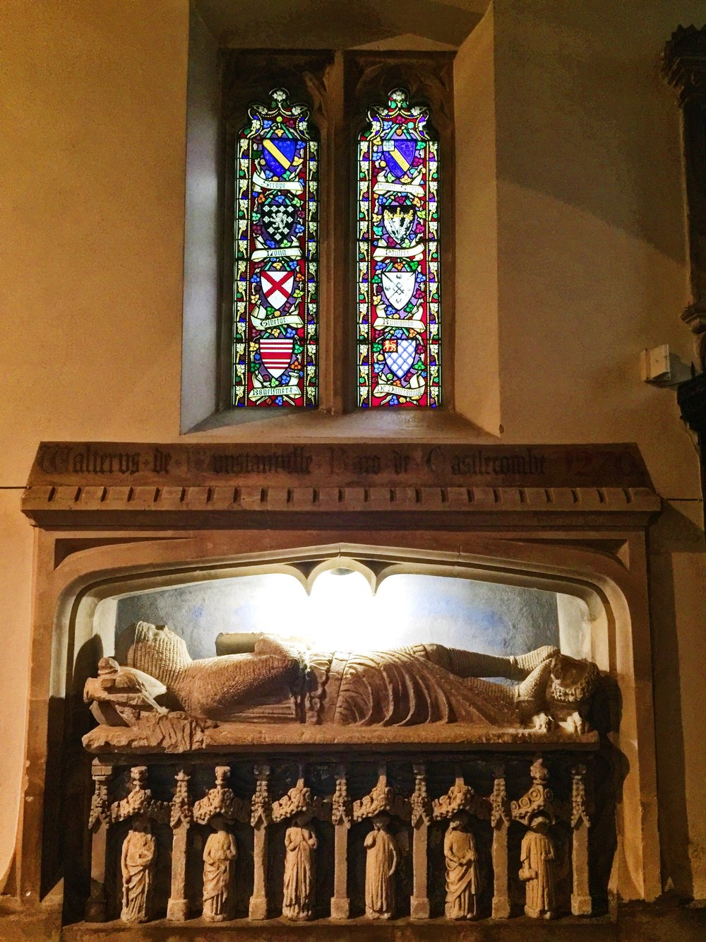 Sir Walter's effigy with 13th century dedication above. Stained glass with crests of important families in the region