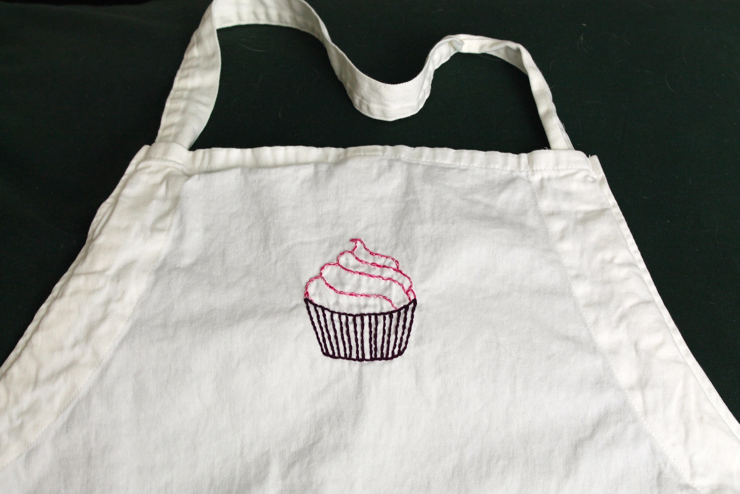 Apron with hand embroidered cupcake on it