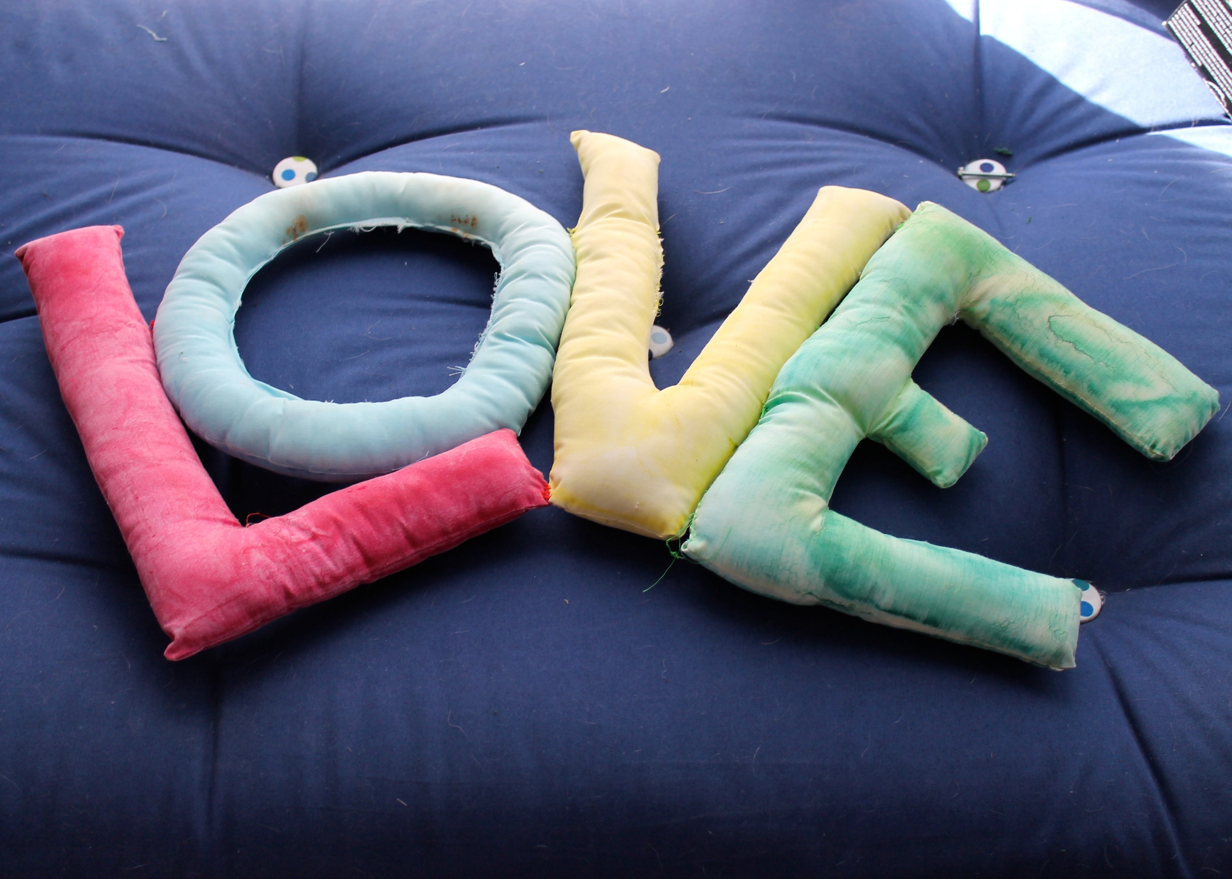 "Stuffed sewn letters spelling out ""love"""