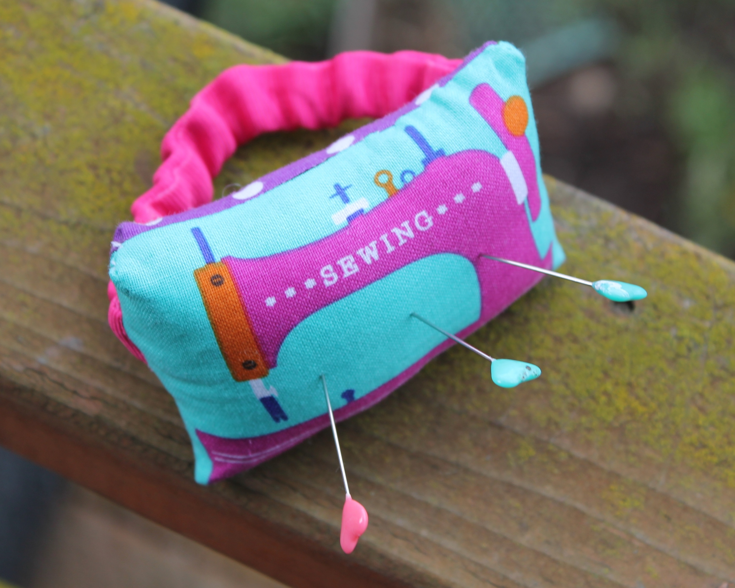 Wrist pincushion with pink sewing machine on it