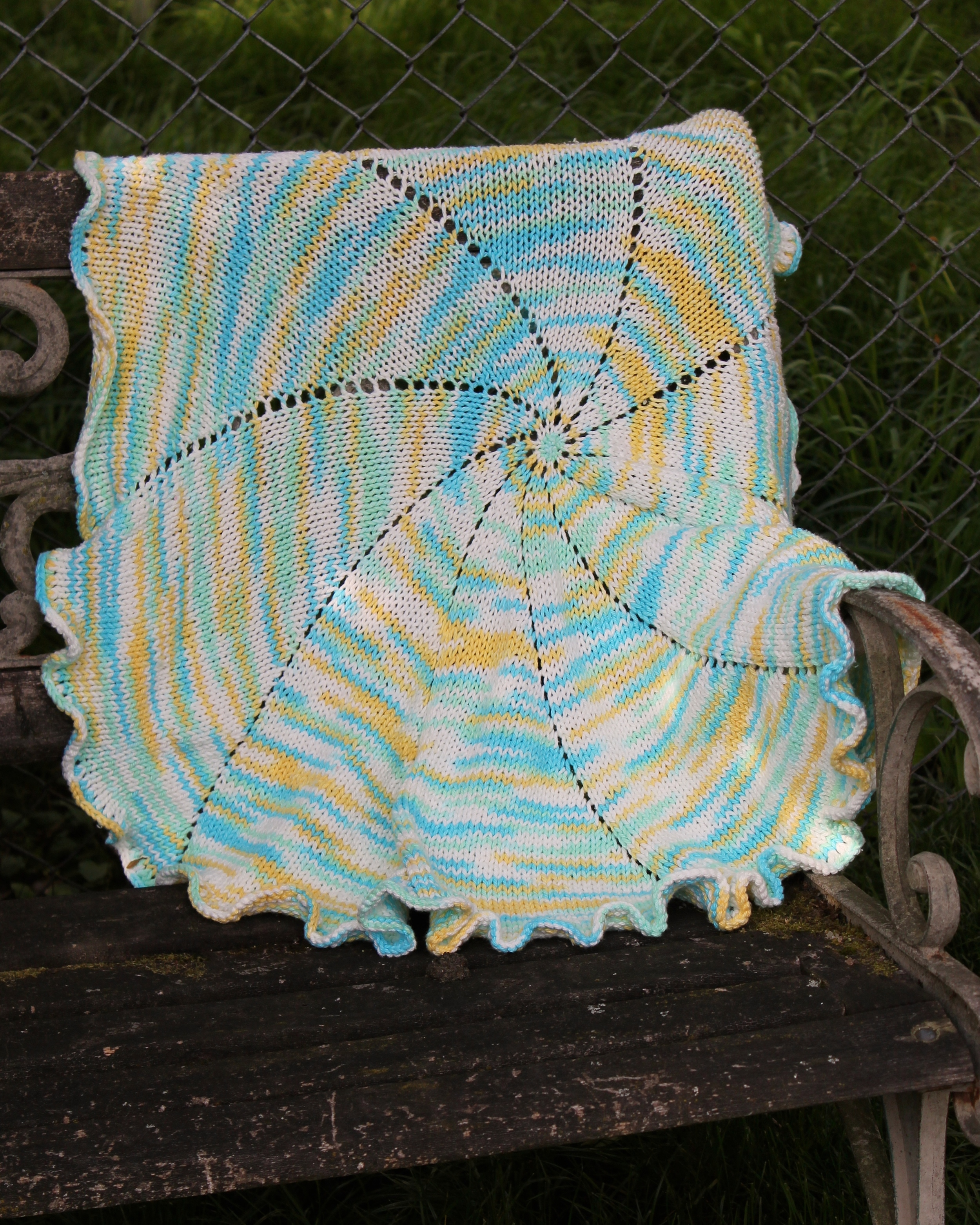 Spiral baby blanket made from variegated blue and yellow cotton yarn