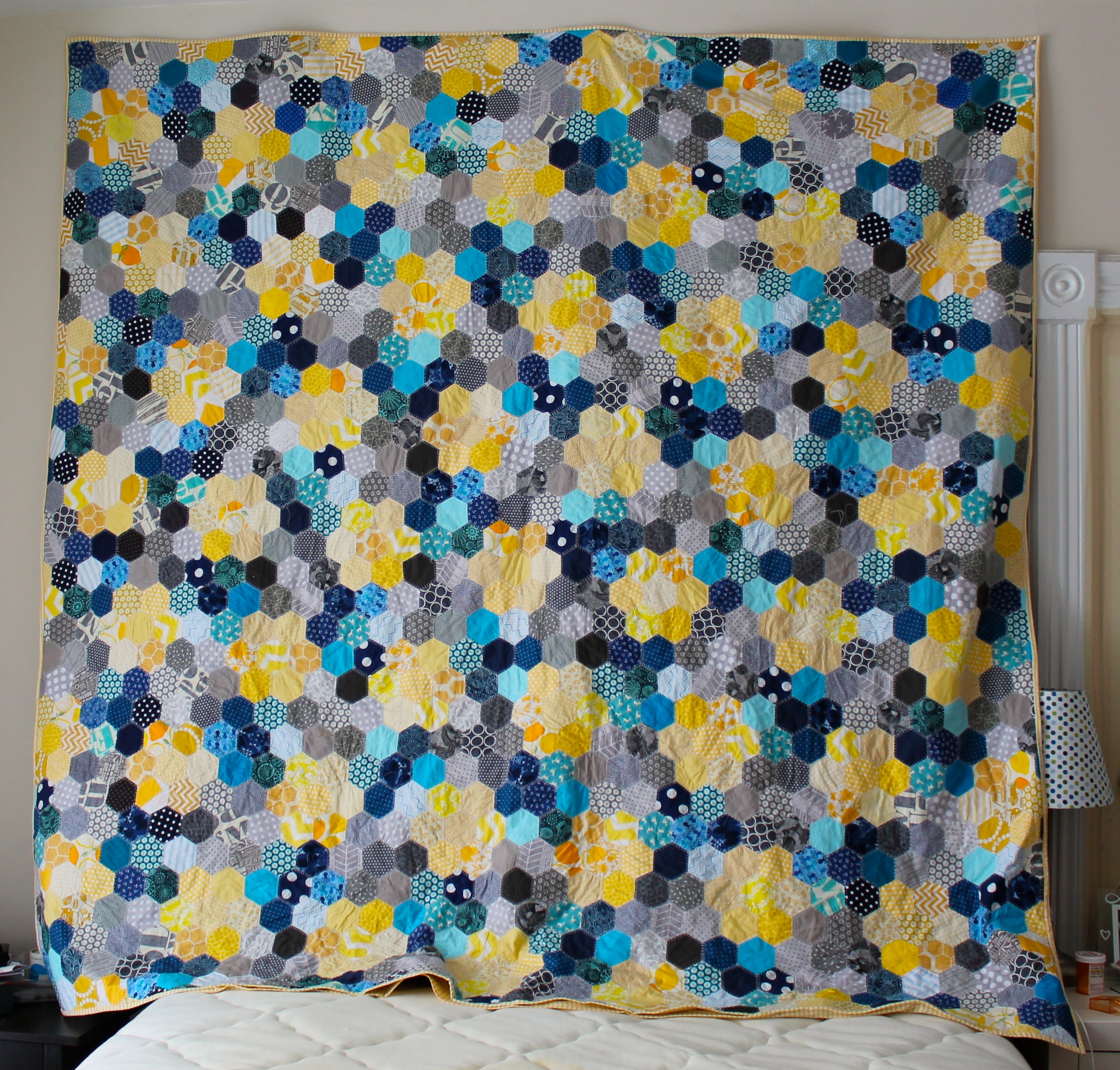 Queen sized hand pieced quilt made with blue, gray, and yellow hexagons