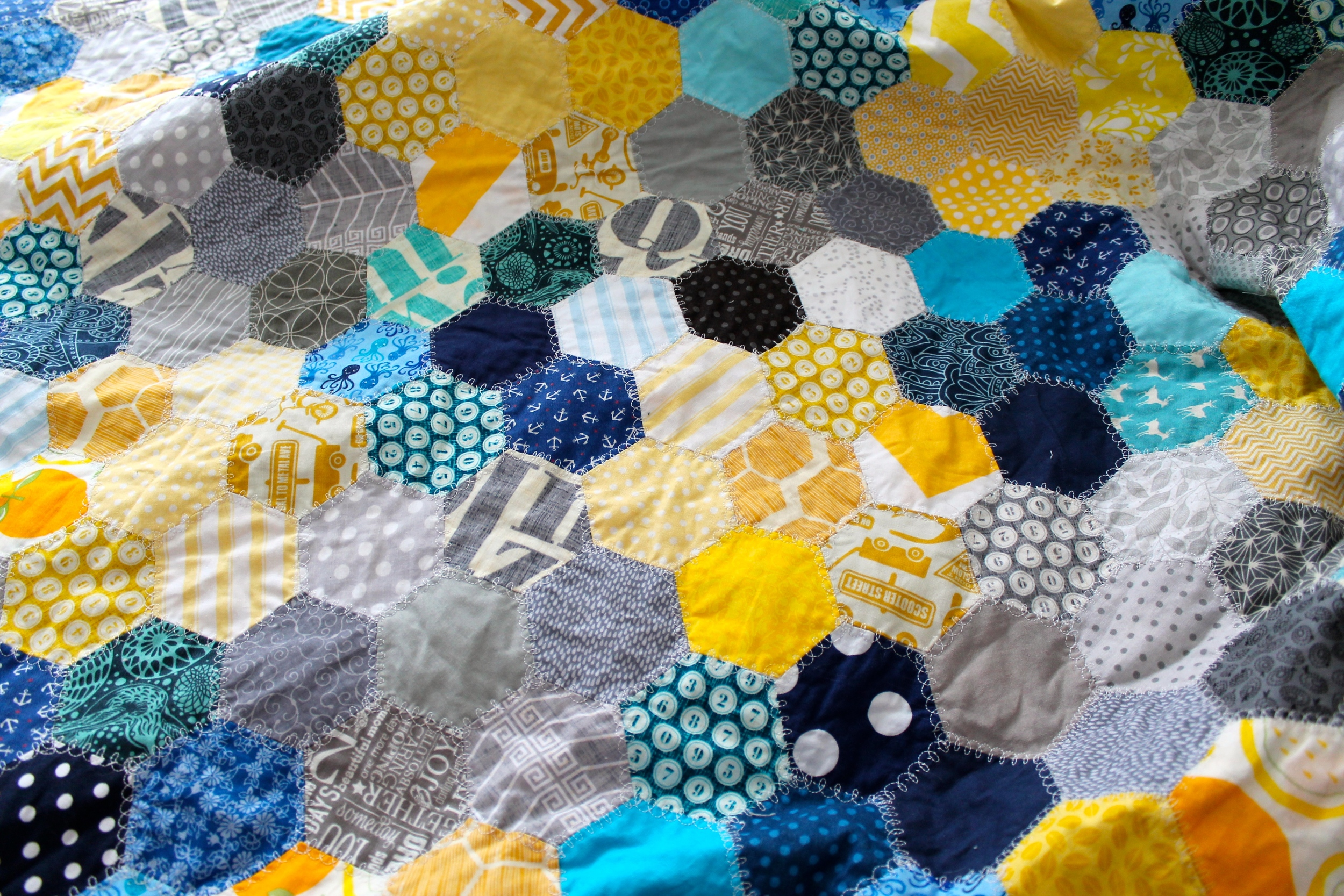 Close up of queen sized hand pieced quilt made with blue, gray, and yellow hexagons