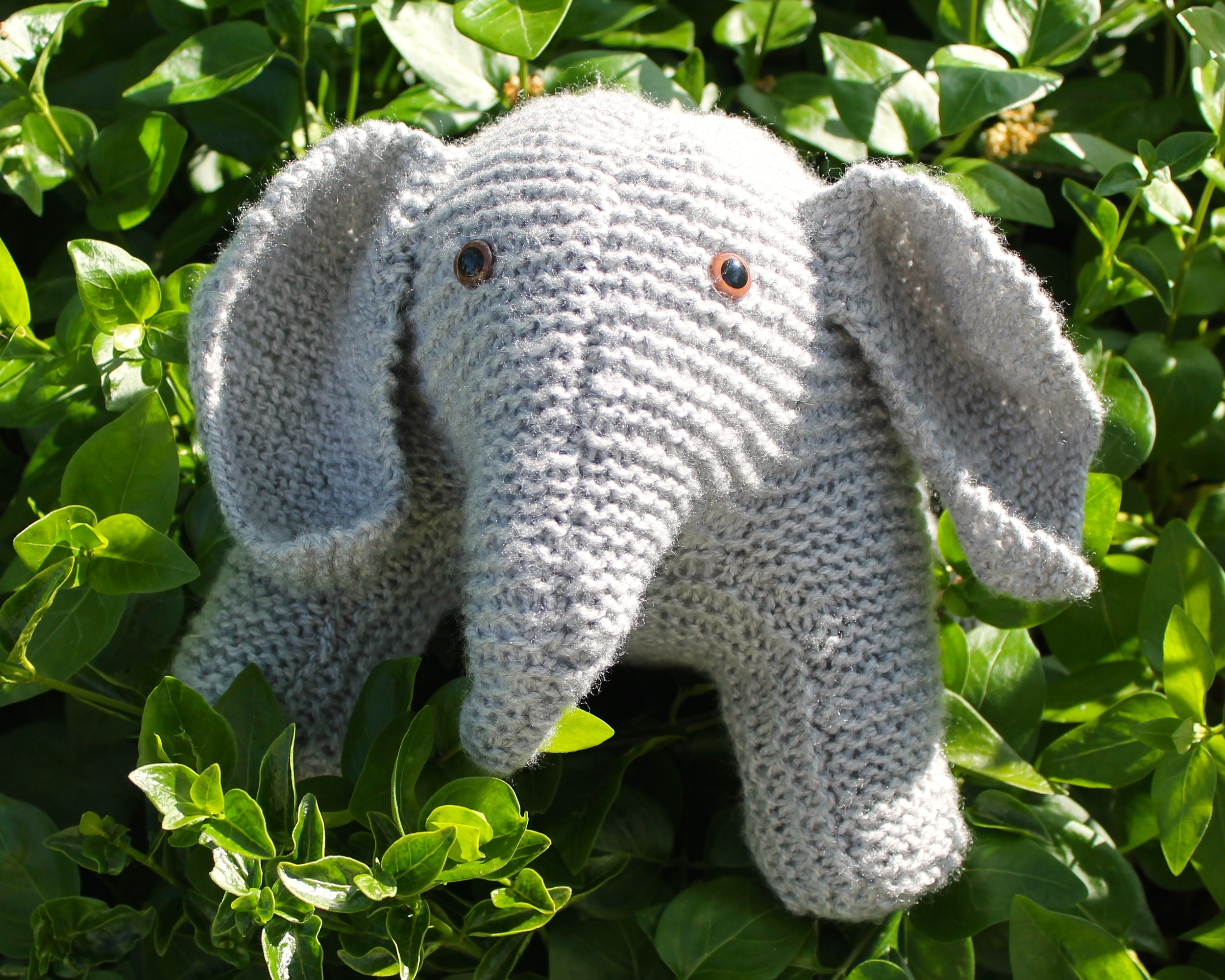 Gray knit stuffed elephant with brown glass eyes, sitting in a bush