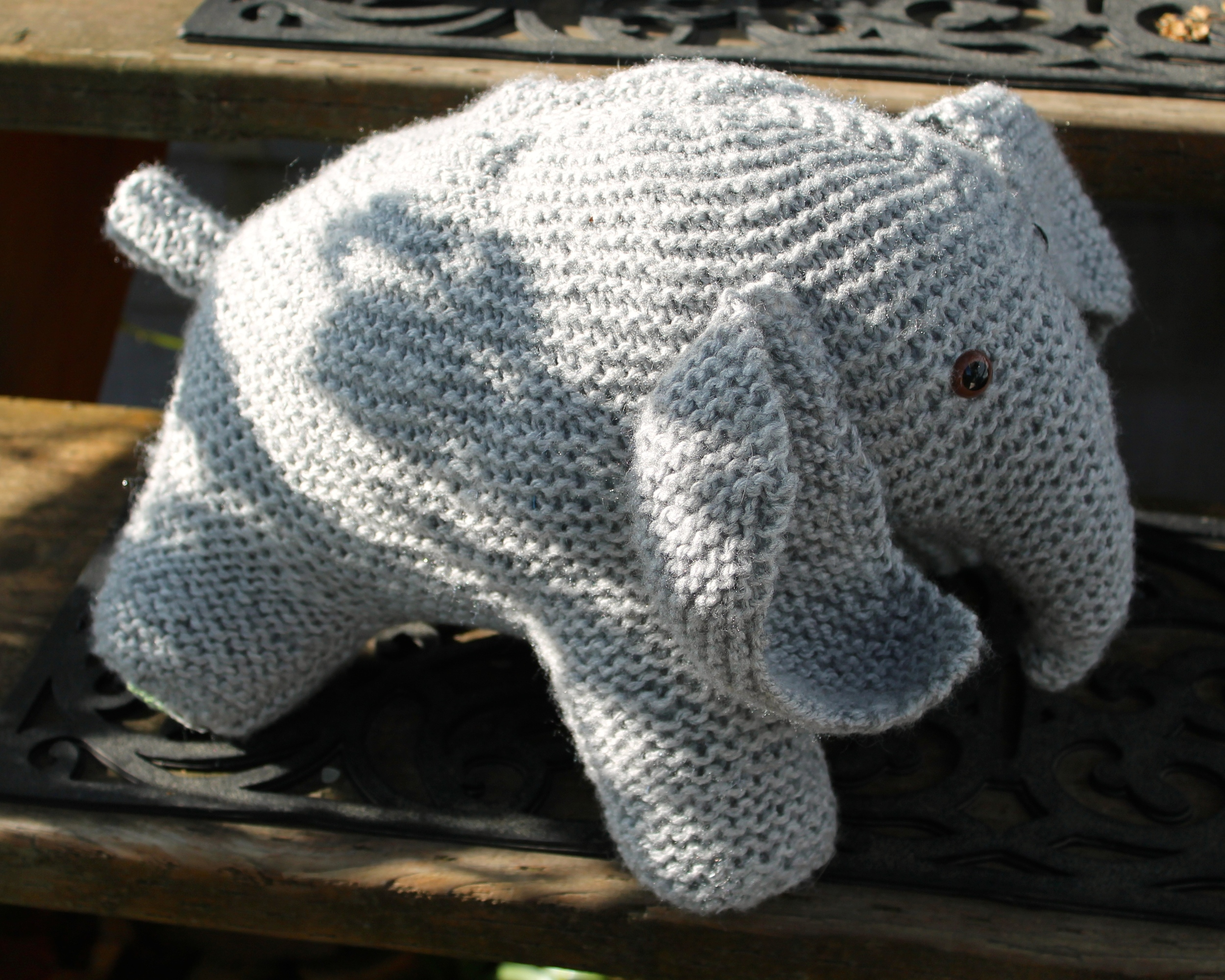Gray knit stuffed elephant with brown glass eyes, sitting in on porch steps